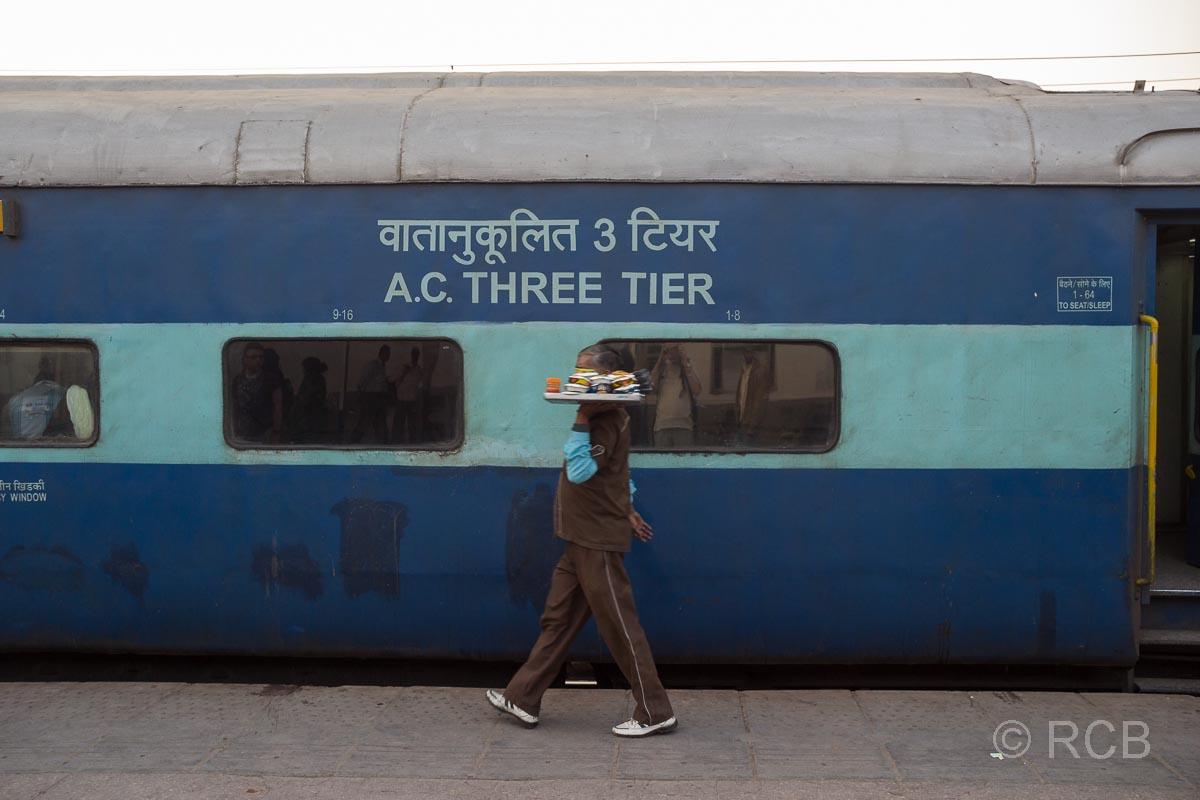 Agra, Kellner geht an einem Zug vorbei im Bahnhof Cantonment