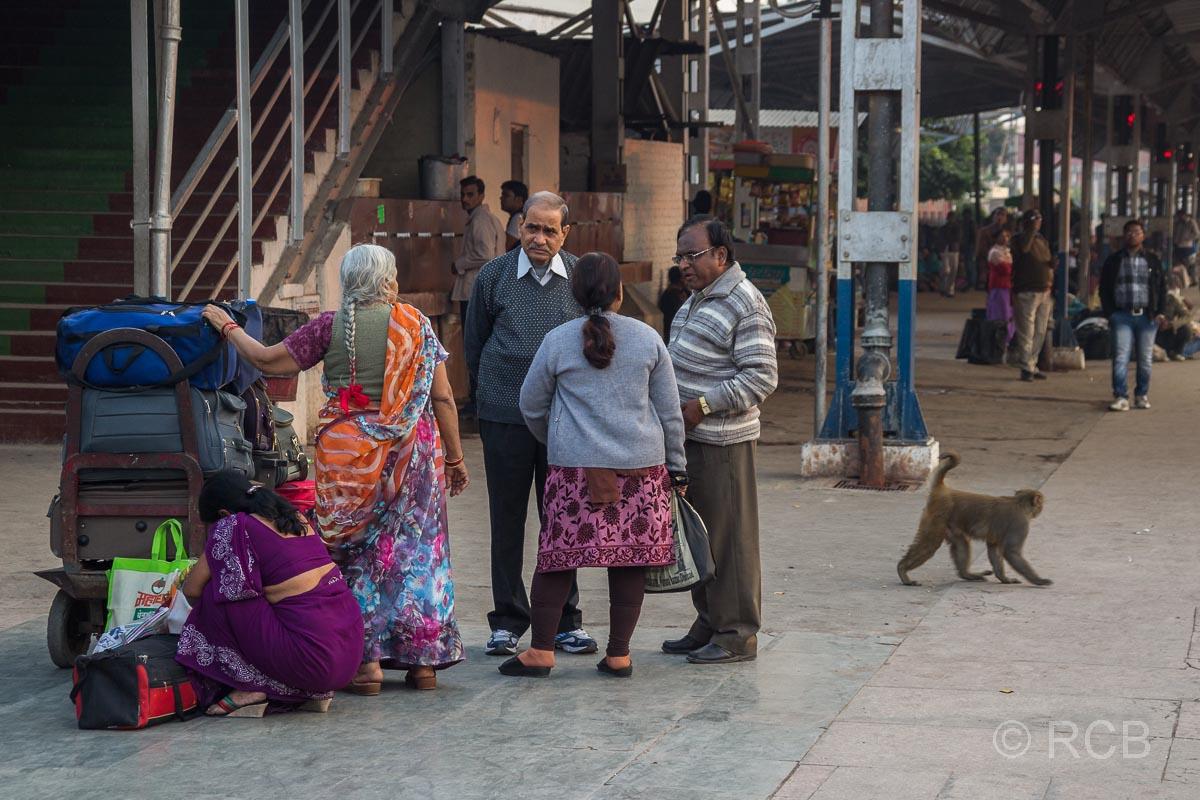 Agra, Menschen und einAffe warten auf dem Bahnsteig im Bahnhof Cantonment