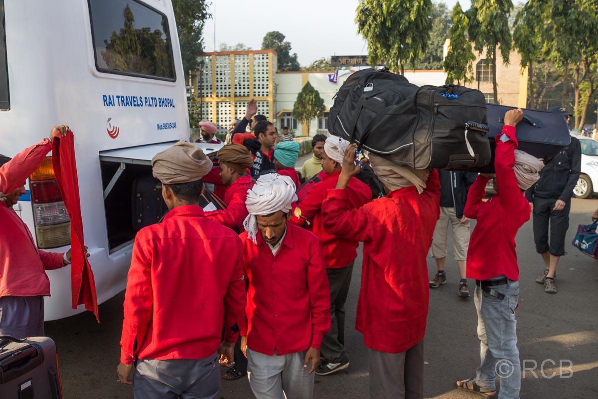 Träger im Bahnhof Jabalpur verladen Gepäck in einen Bus