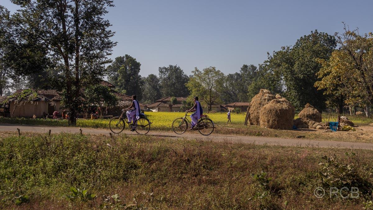 2 Mädchen radeln durch ein Dorf in der Nähe des Kanha National Park