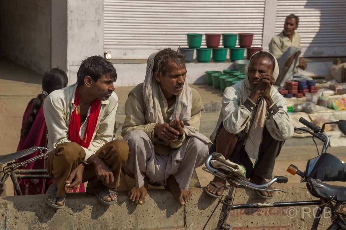 Männer hocken auf einer Mauer am Straßenrand auf der Fahrt durch Uttar Pradesh