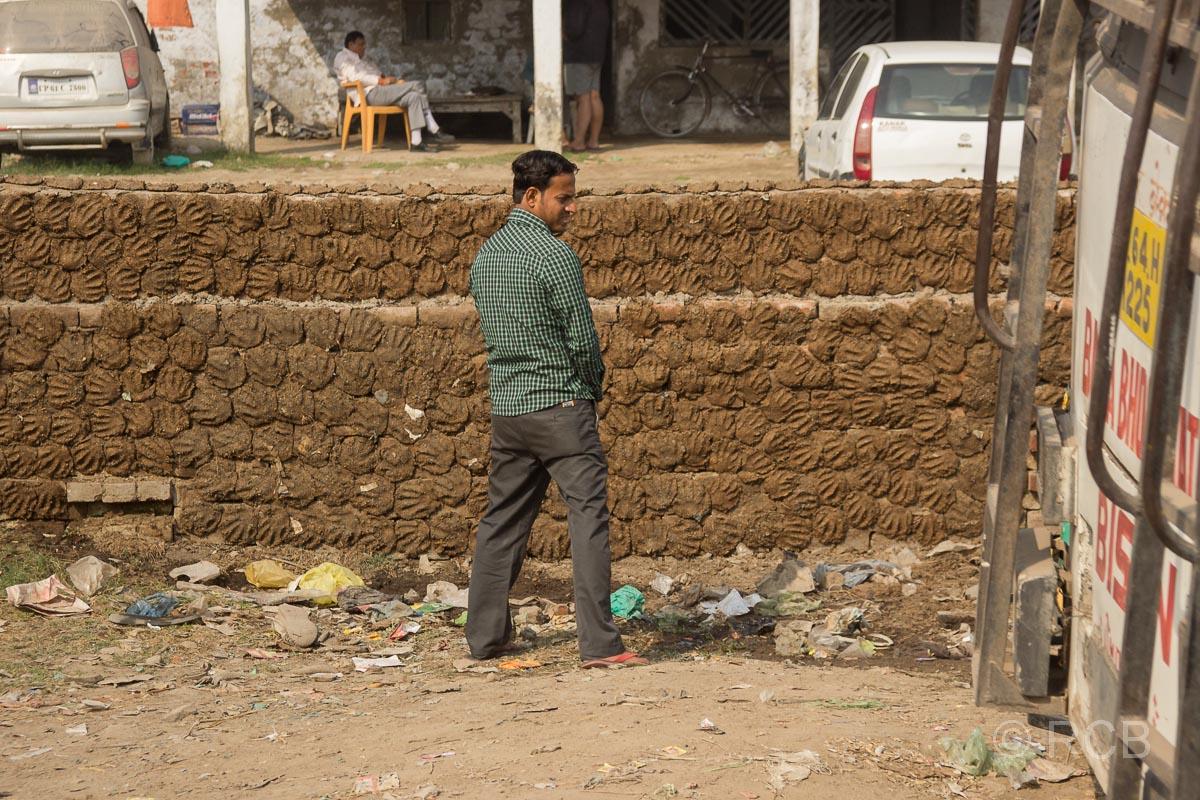 Fahrt durch Uttar Pradesh, Mann uriniert am Straßenrand