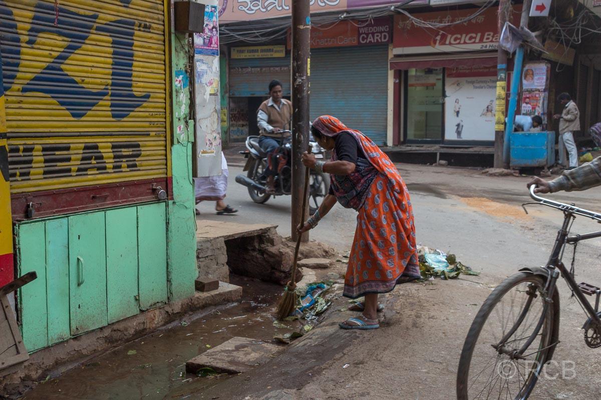 Varanasi, Frau fegt den Rinnstein in der Altstadt