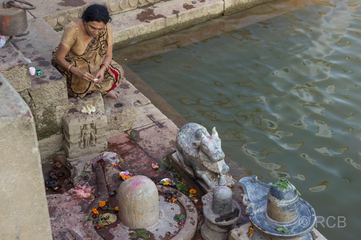 Varanasi, an den Ghats, Frau bringt Opfer dar