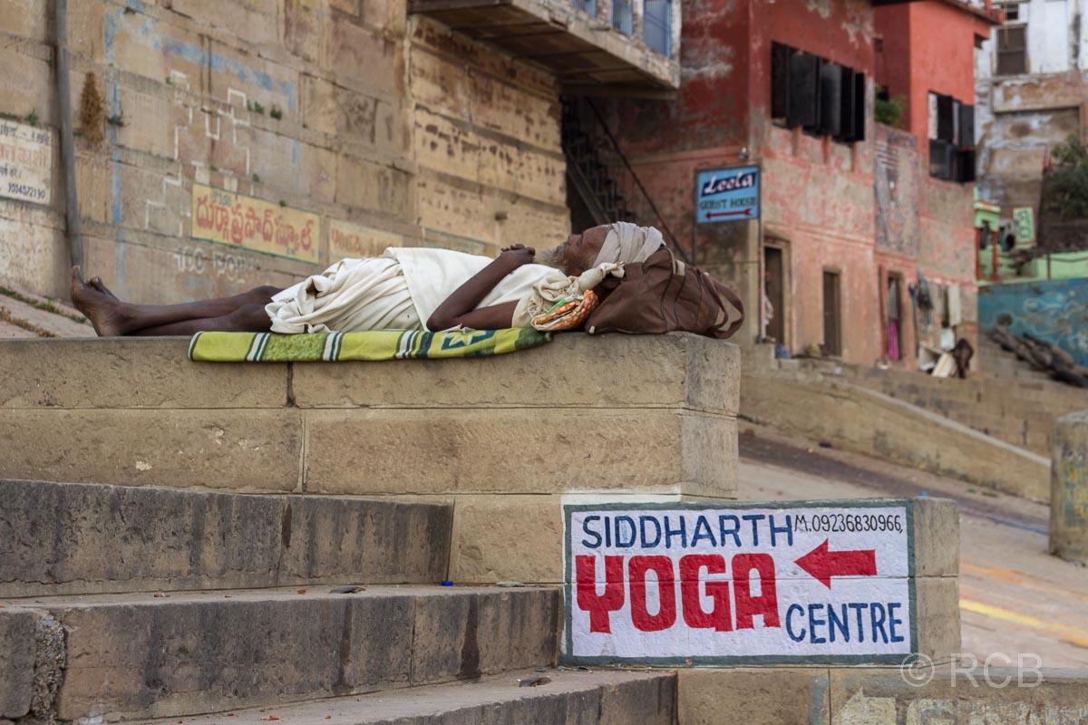 Varanasi, an den Ghats, Mann liegt entspannt auf den Stufen neben einem Werbeschild für ein Yoga-Zentrum