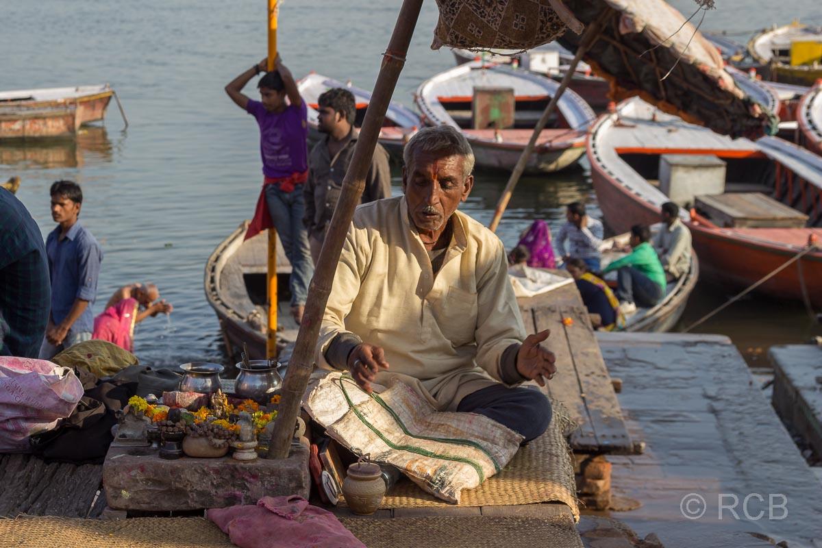 Varanasi, Mann unter einem Sonnenschirm an den Ghats