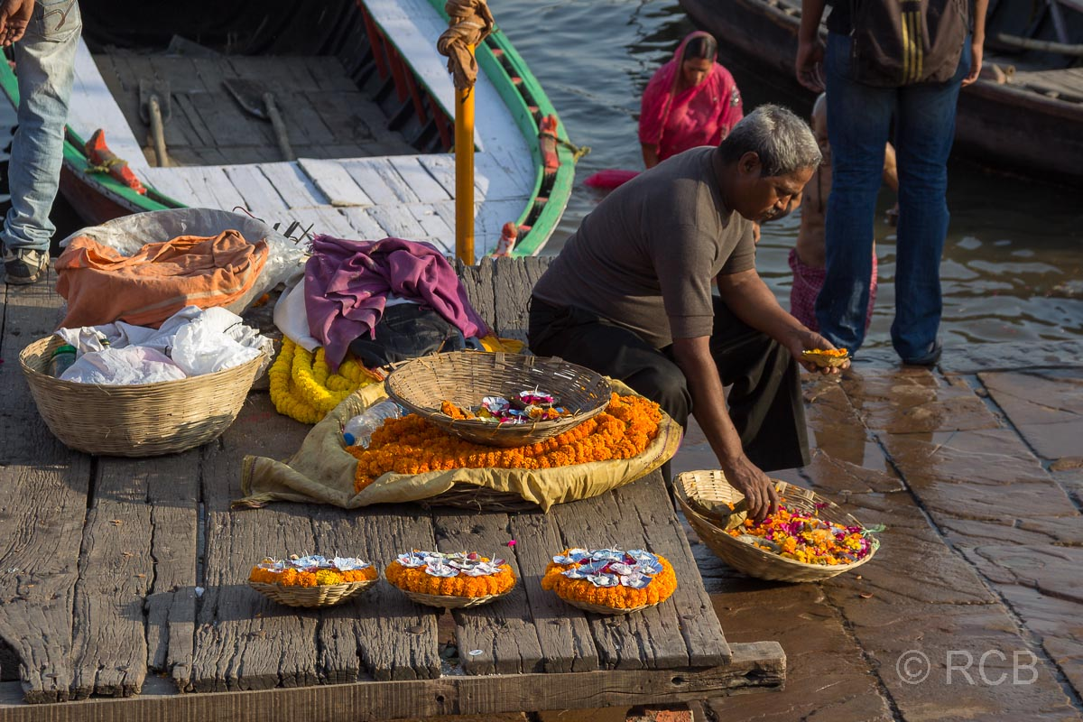 Varanasi, Mann präpariert Blumenschiffchen zum Verkauf an den Ghats