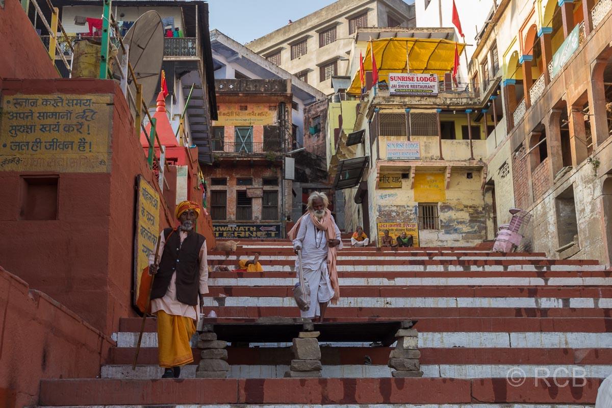 Varanasi, Sadhus steigen an den Ghats eine Treppe hinunter