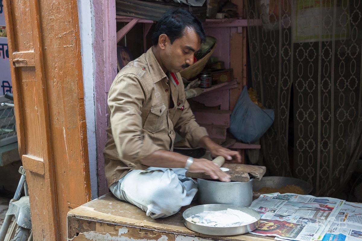 Varanasi, Mann in der Altstadt rollt Teigfladen aus und kaut dabei Betel