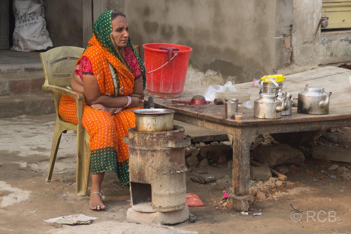 Varanasi, Frau sitzt am Straßenrand und kocht auf einem Kanonenofen