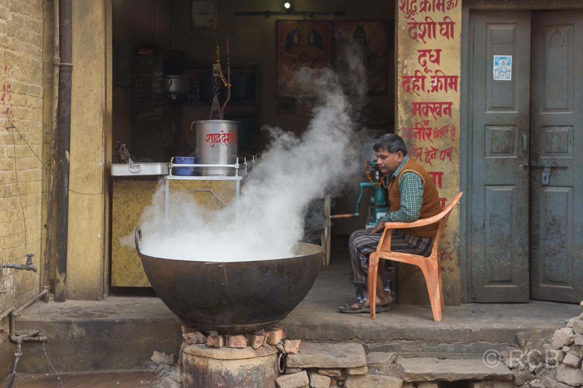 Varanasi, Mann erhitzt einen großen, dampfenden Kessel am Straßenrand