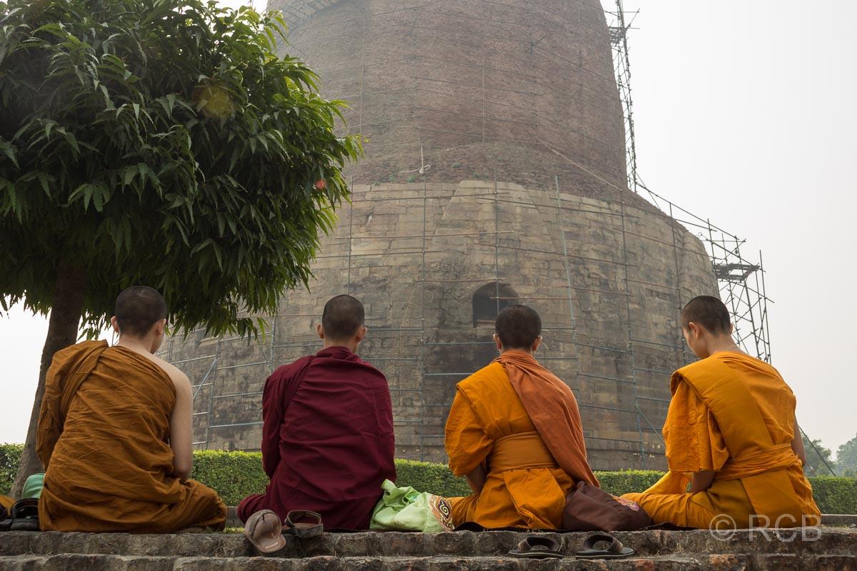 Sarnath, buddhistische Mönche sitzen vor einer großen Stupa