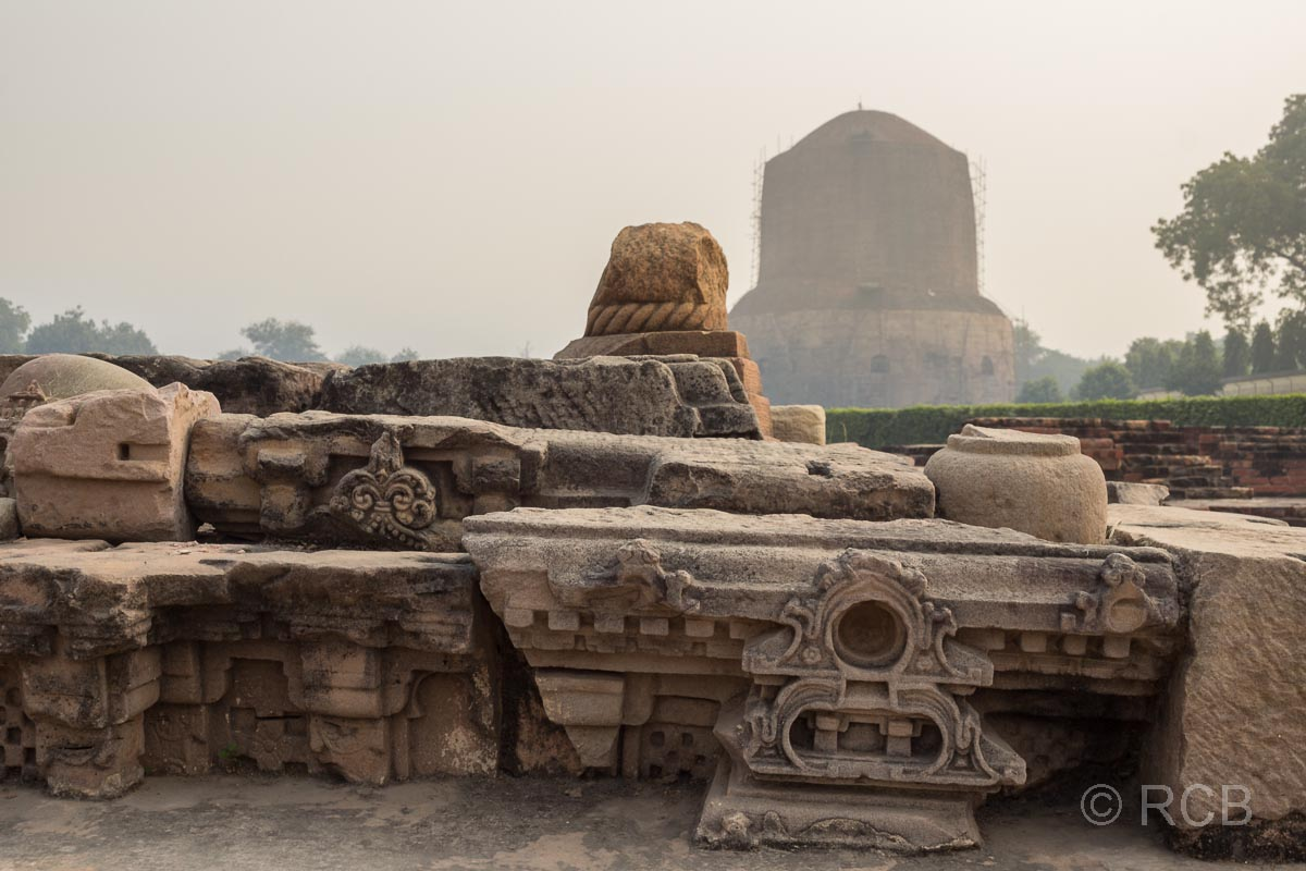 Sarnath, Friese aus den Tempelruinen, im Hintergrund eine große Stupa