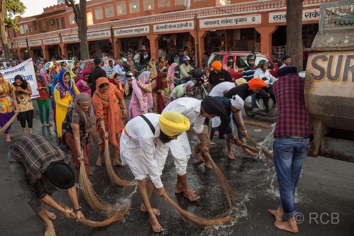 barfüßige Männer reinigen die Straße bei einem Sikh-Umzug, Jaipur, Altstadt