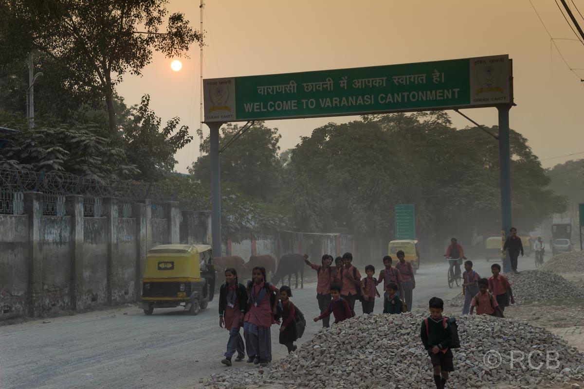 Varanasi, Kinder auf einer Schotterstraße bei untergehender Sonne im Dunst