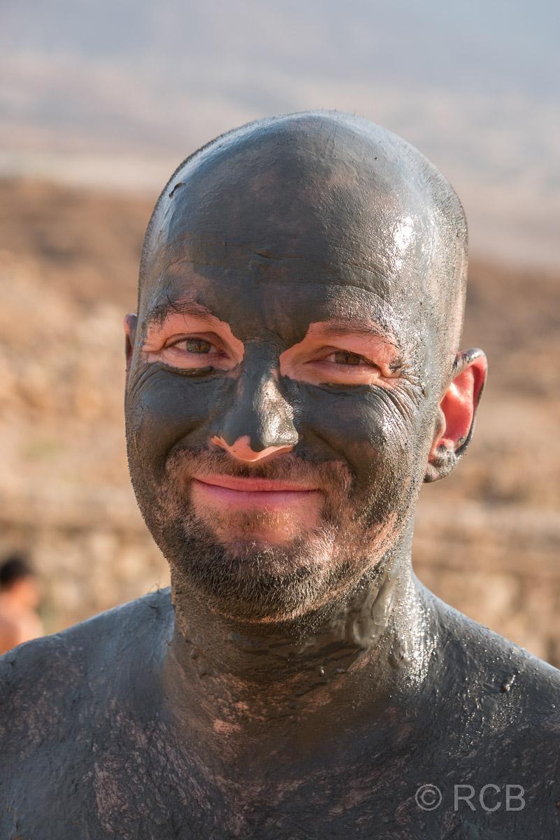Mann ist komplett eingeschmiert mit Heilschlamm aus dem Toten Meer
