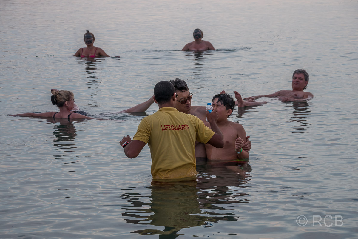 Bademeister spülte einem Jungen die Augen, der Salzwasser aus dem Toten Meer darein bekommen hat.