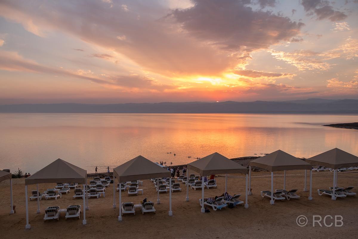 Sonnenuntergang hinter lauter leeren Liegestühlen am Toten Meer
