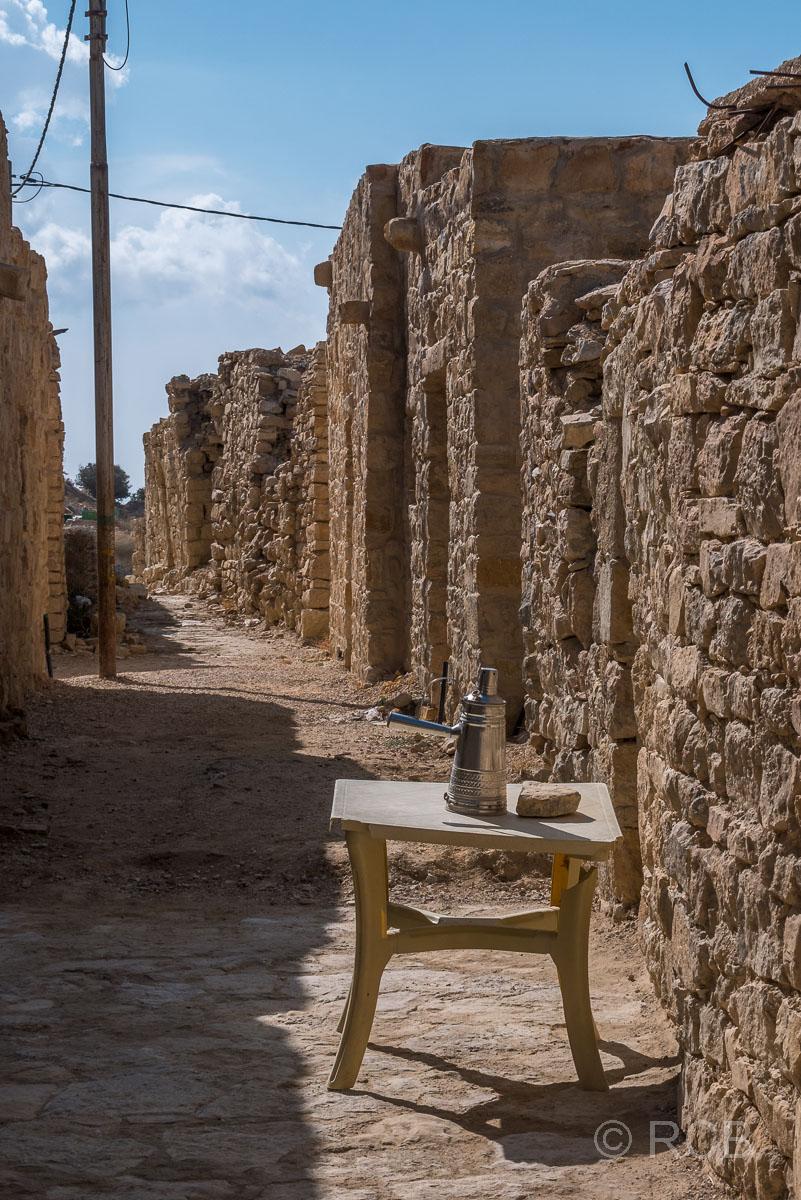 Tisch mit Kaffeekanne in einer Gasse im Dorf Dana