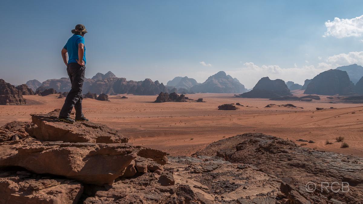 Mann überblickt das Wadi Rum von einem erhöhten Felsen aus