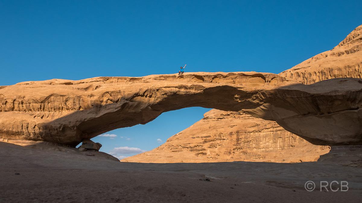 Mann sitzt ganz klein auf dem riesigen Felsbogen Al Kharaz