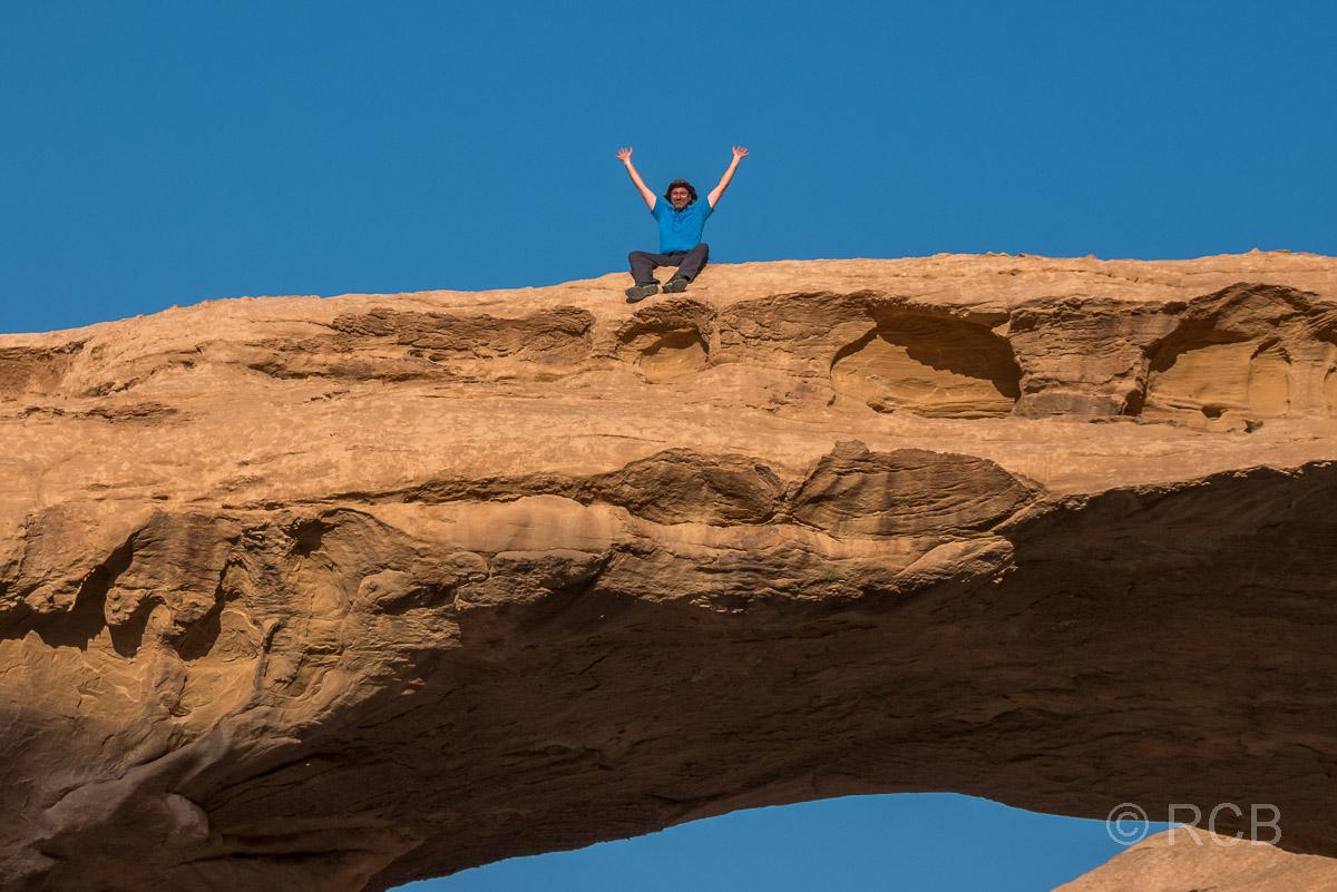 Mann sitzt auf dem Felsbogen Al Kharaz