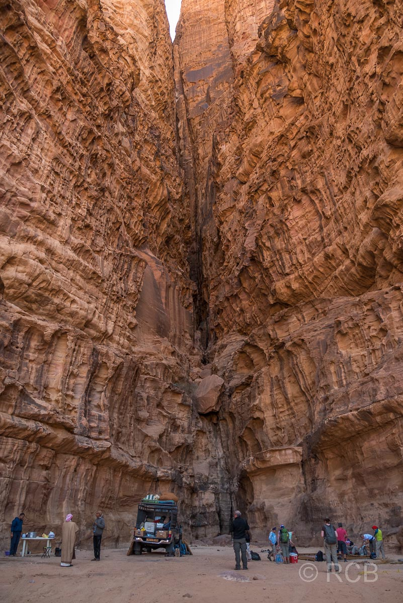 Wandergruppe bei der Mittagsrast im Schatten hoher Felswände im Wadi Rum