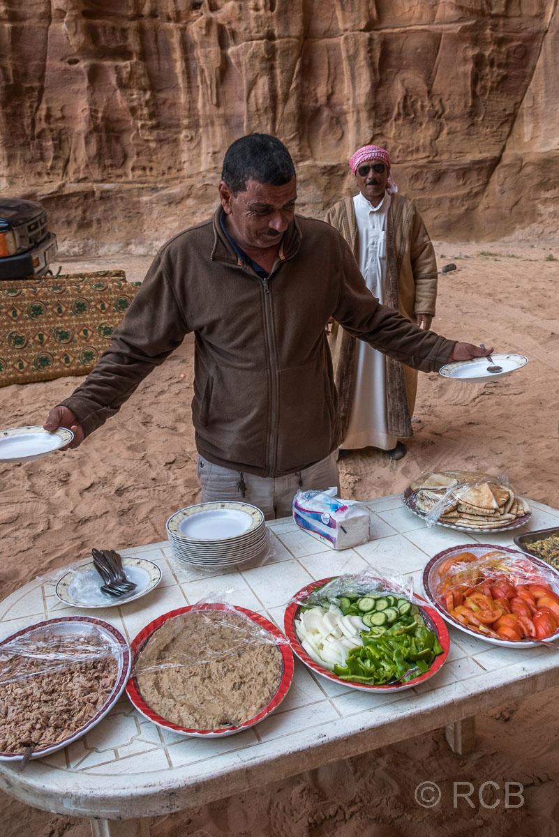 Beduine präsentiert das Mittagsbüffet für eine Wandergruppe auf ihrer Rast im Wadi Rum