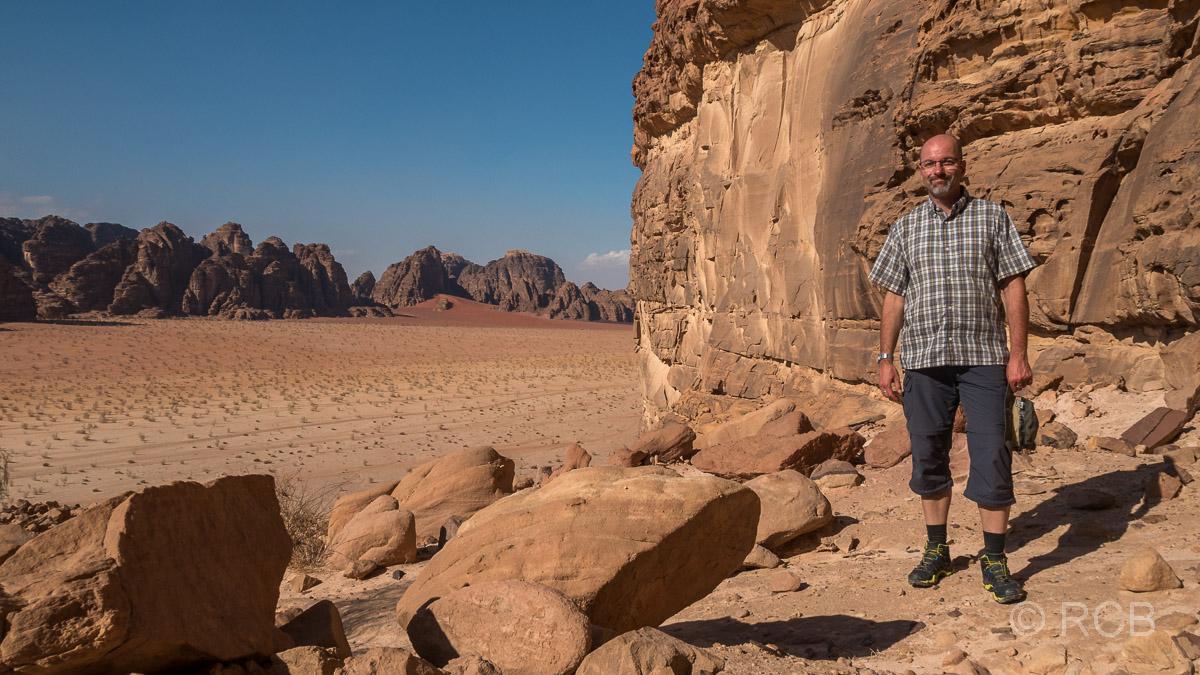 Mann steht auf einem Felsplateau im Wadi Rum