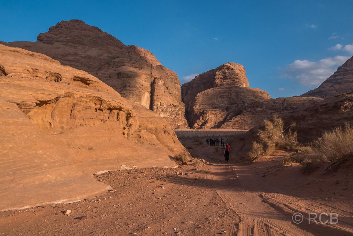 Wanderer bei Abendsonne in einer Felspassage im Wadi Rum