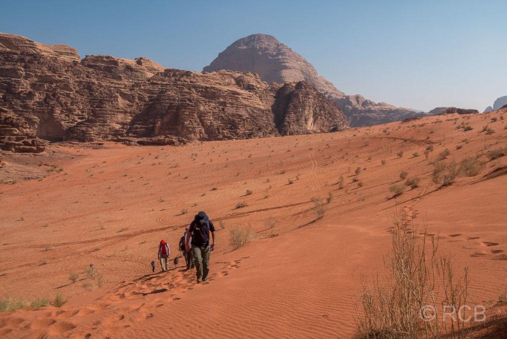 Wanderer steigen auf die höchste Sanddüne des Wadi Rum