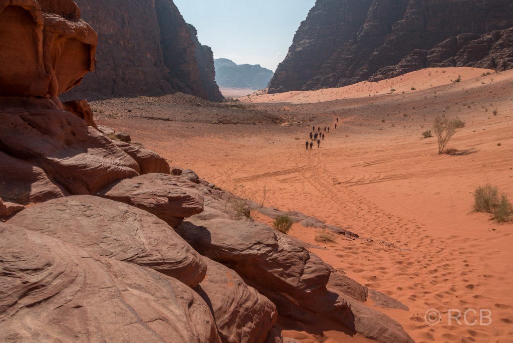Wanderer entfernen sich von der höchsten Sanddüne des Wadi Rum