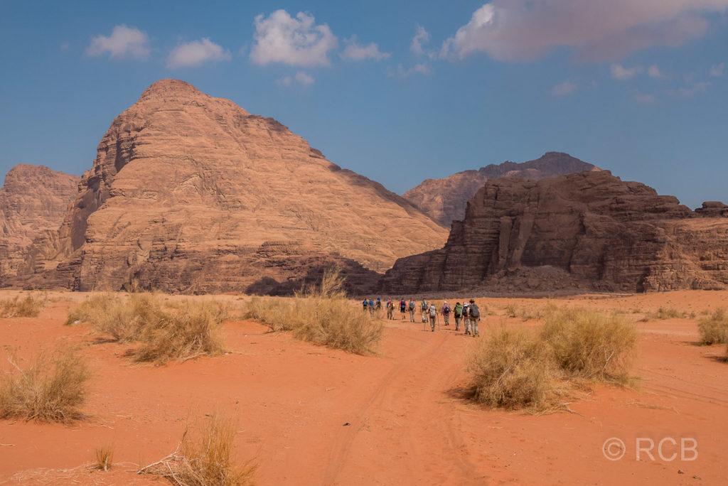 Wanderer laufen im Wadi Rum auf Felsen zu
