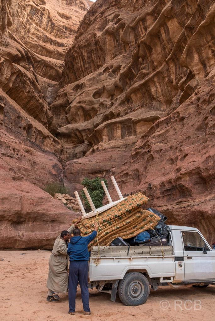 Beduinen laden Sitzkissen und einen Tisch auf einen Pickup im Wadi Rum
