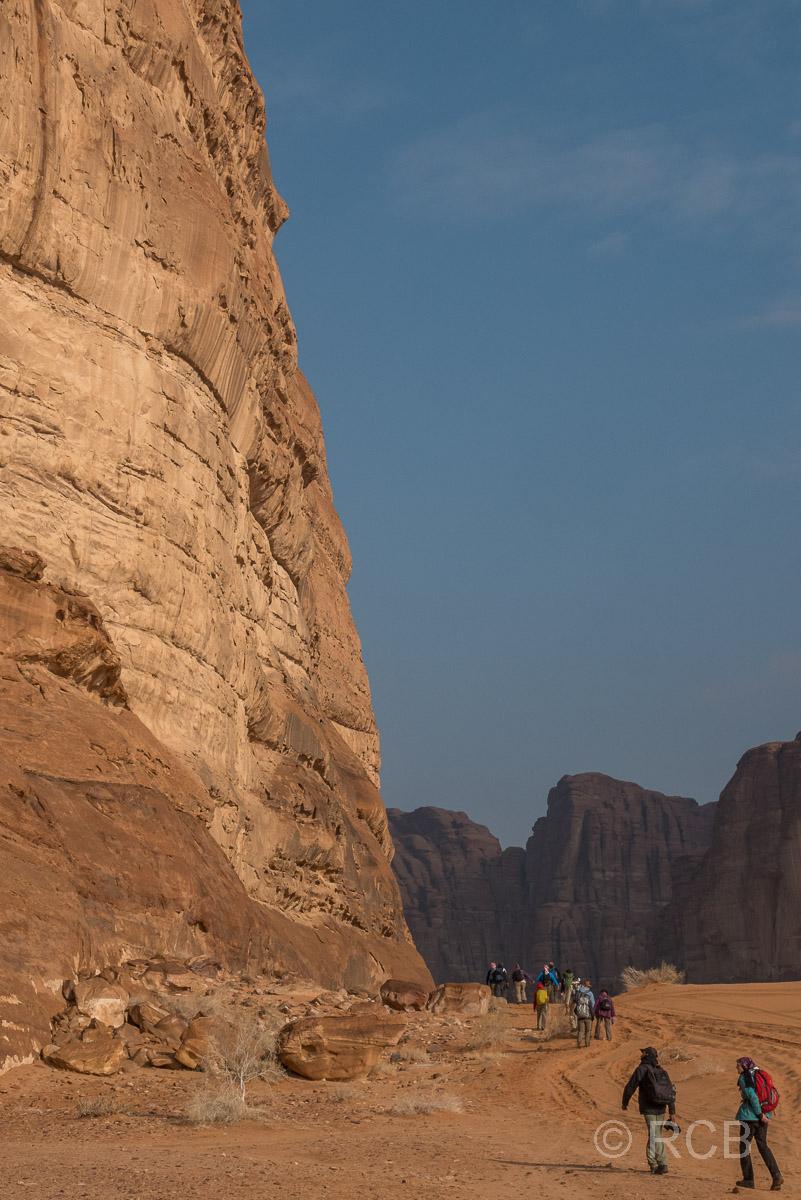 Wanderer passieren die Flanke eines riesigen Felses im Wadi Rum