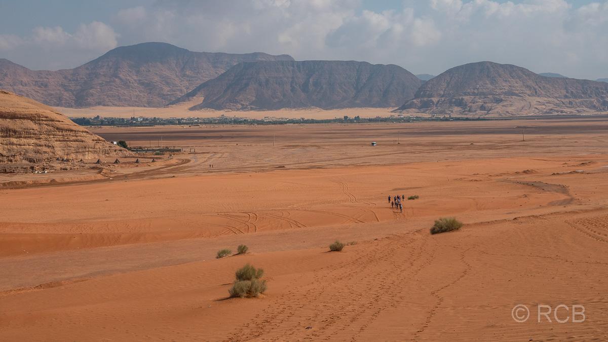 Wanderer laufen in der Ferne auf eine Siedlung am Rande des Wadi Rum zu.