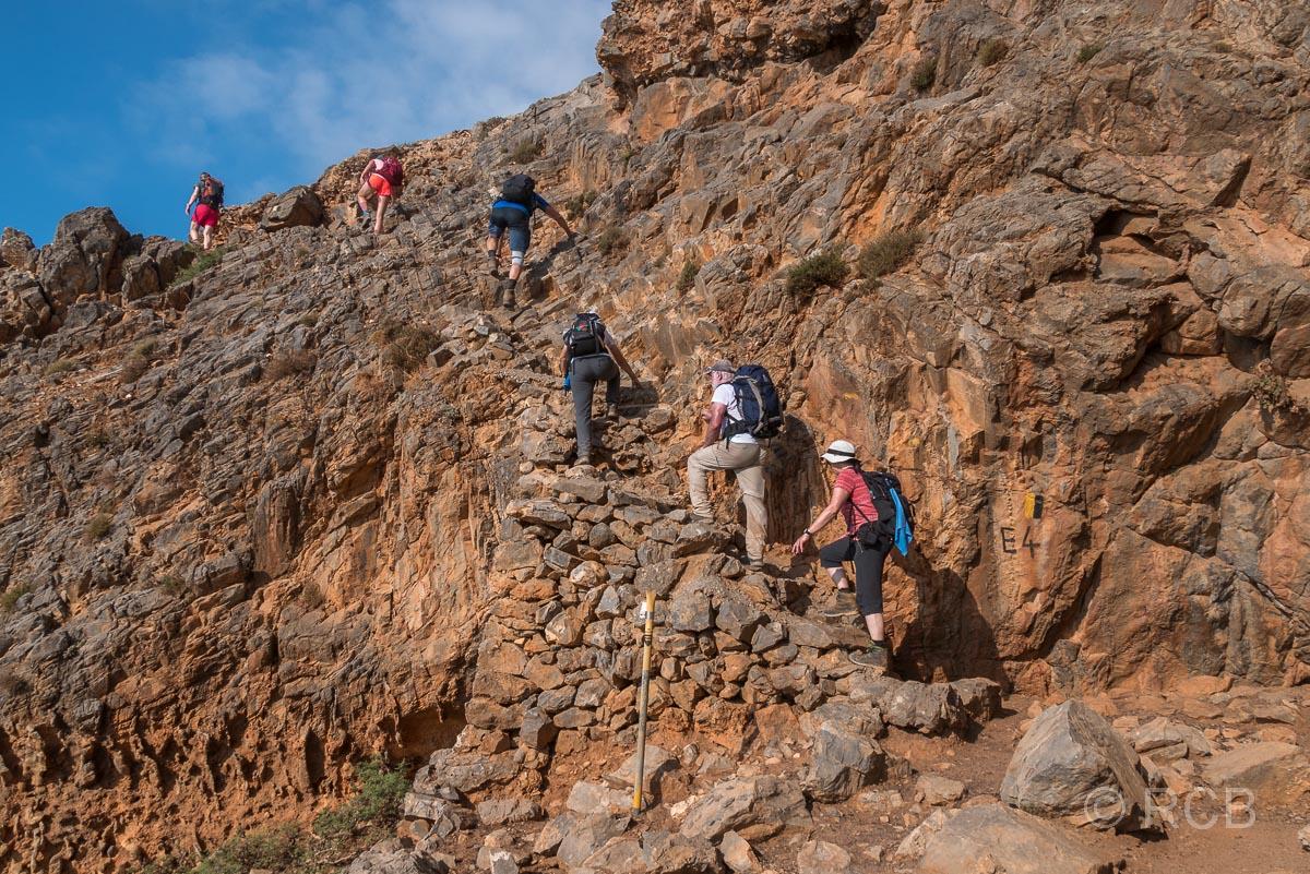 Wanderer ersteigen eine Treppe bei einem ausgesetzten Aufstieg auf dem Küstenpfad des E4