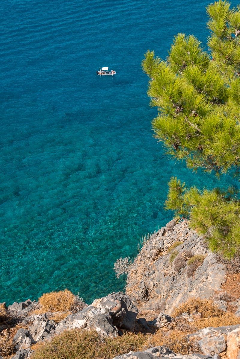 Bucht mit türkisblauem Wasser einer grünen Kiefer und einem kleinen Boot