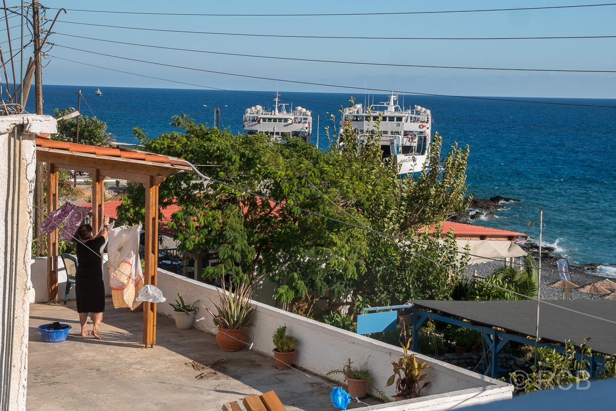 Blick von meinem Hotelbalkon auf den Fähranleger von Agia Roumeli mit 2 Fähren, im Vordergrund hängt eine Frau Wäsche auf ihrem Balkon auf