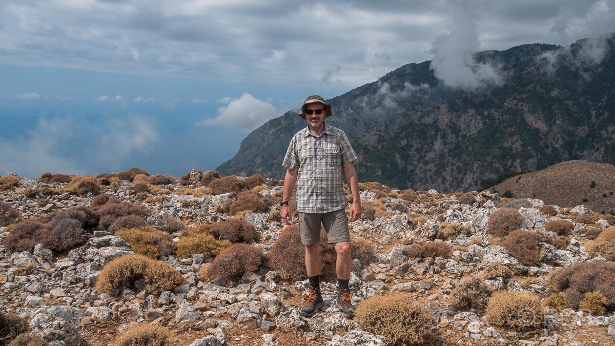 Mann steht am Gipfel des Papouras