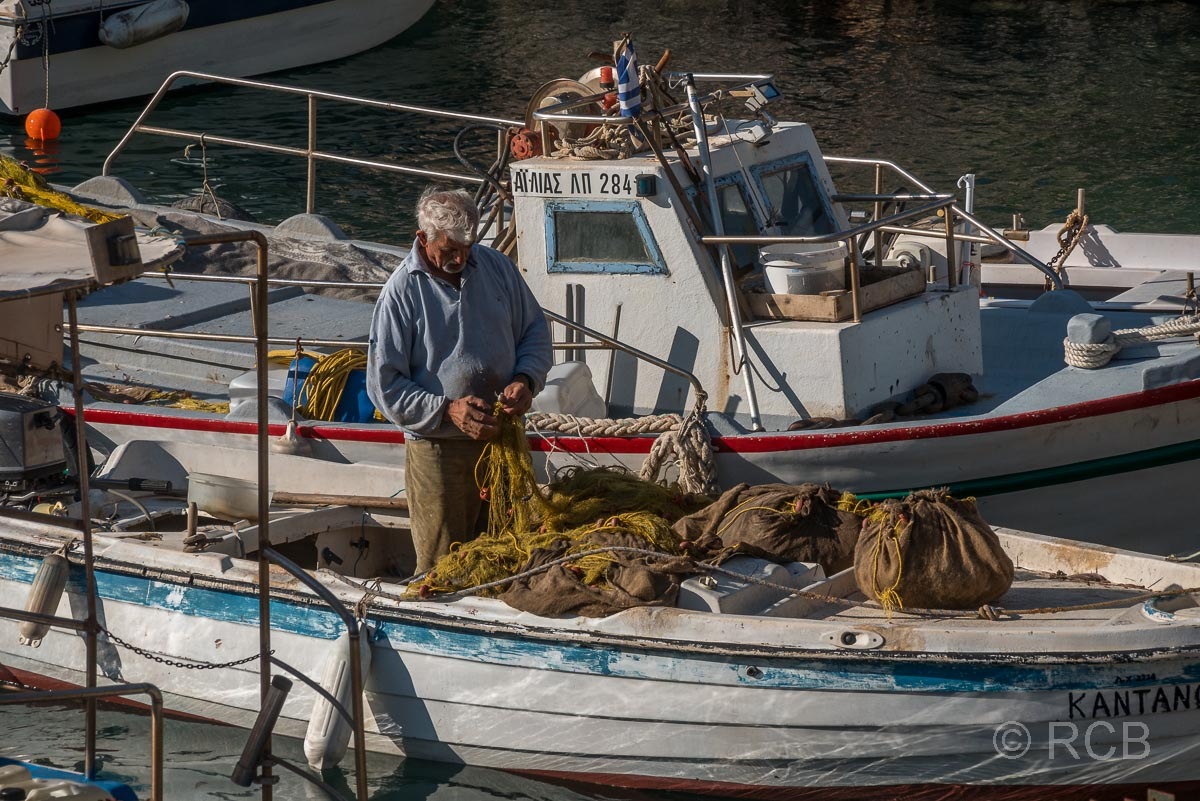 Fischer in seinem Boot beim Flicken der Netze im Hafen von Sougia
