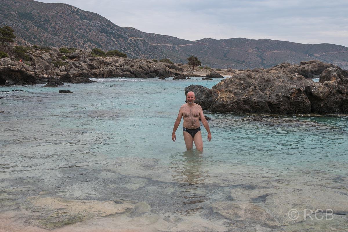 Mann im Wasser in einer Badebucht am Wanderweg E4
