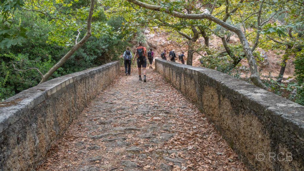 Wanderer passieren eine Brücke mit Herbstlaub in Azogyres