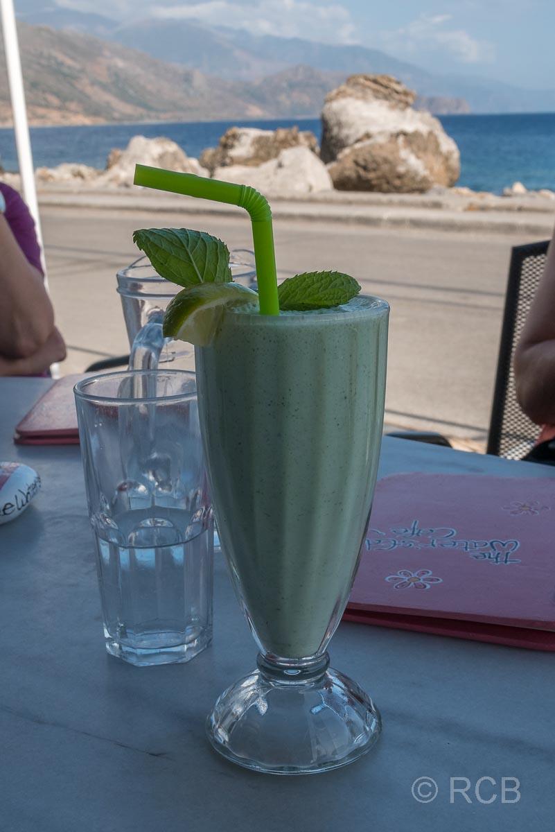 ein grüner Smoothie steht in einem Lokal mit Blick auf's Meer auf dem Tisch
