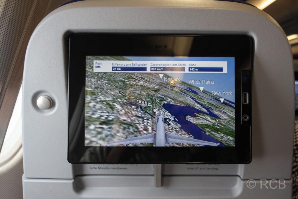 Monitor im Flugzeugsitz mit dem Bild eines Flugzeugs im Anflug auf Newark