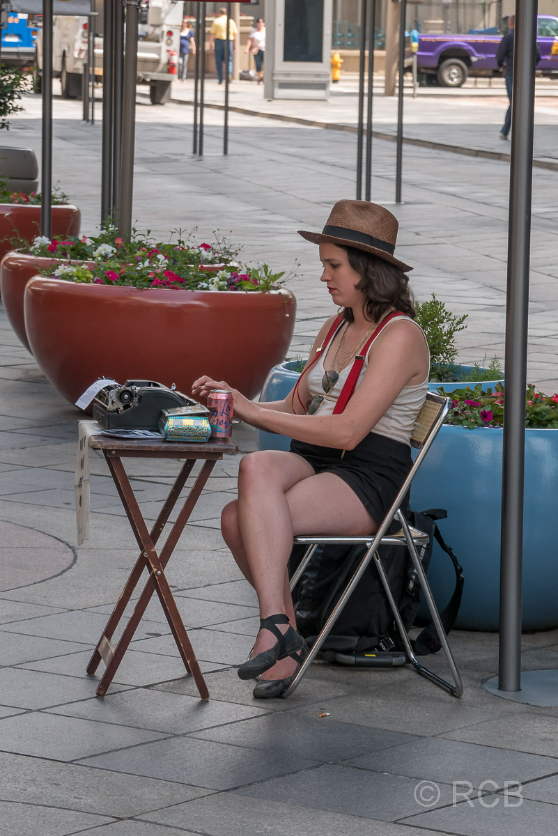 Frau sitzt an Schreibmaschine in der 16th Street Mall