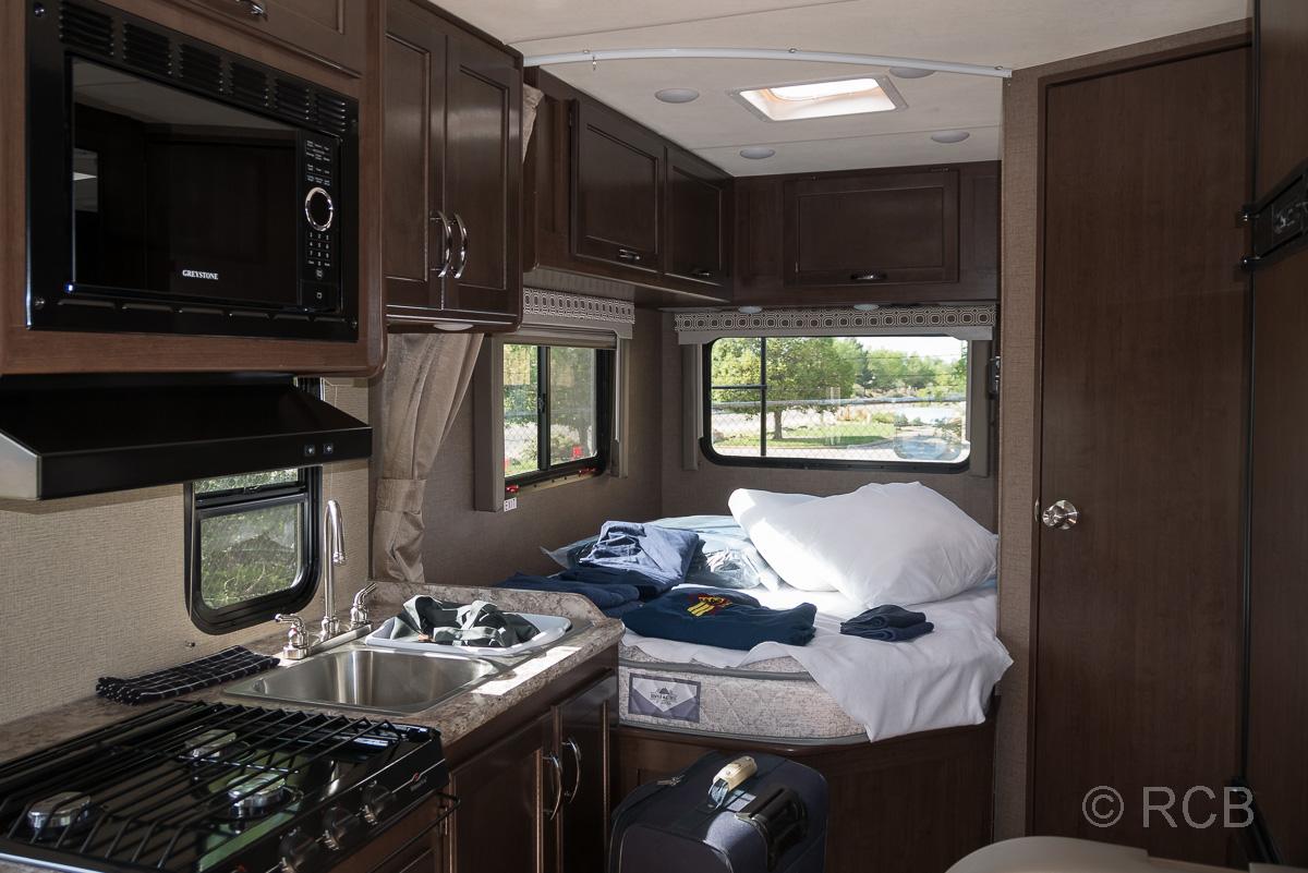 Blick in ein Wohnmobil mit Kochecke und Bett