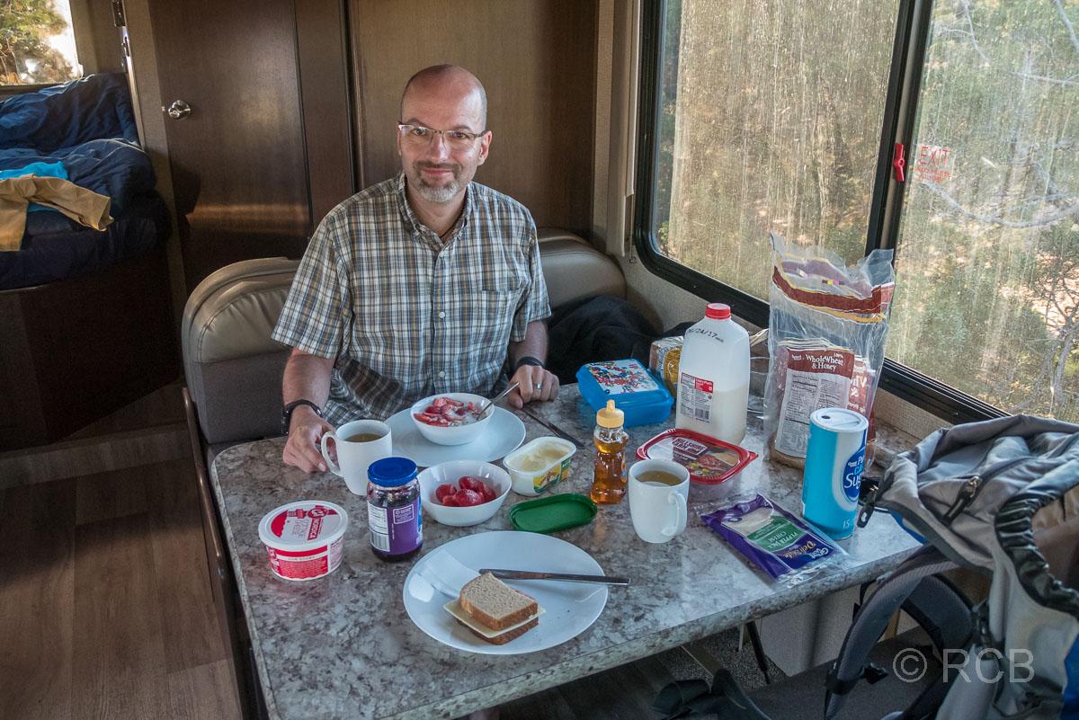 Mann frühstückt im Wohnmobil