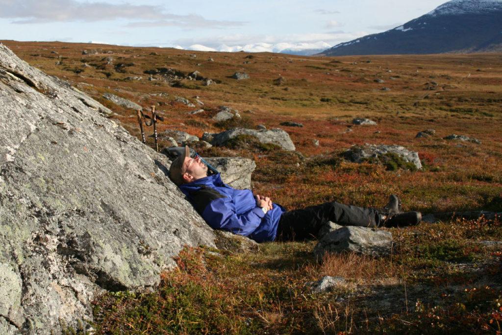 Wanderer ruht sich an einem Fels liegend aus.