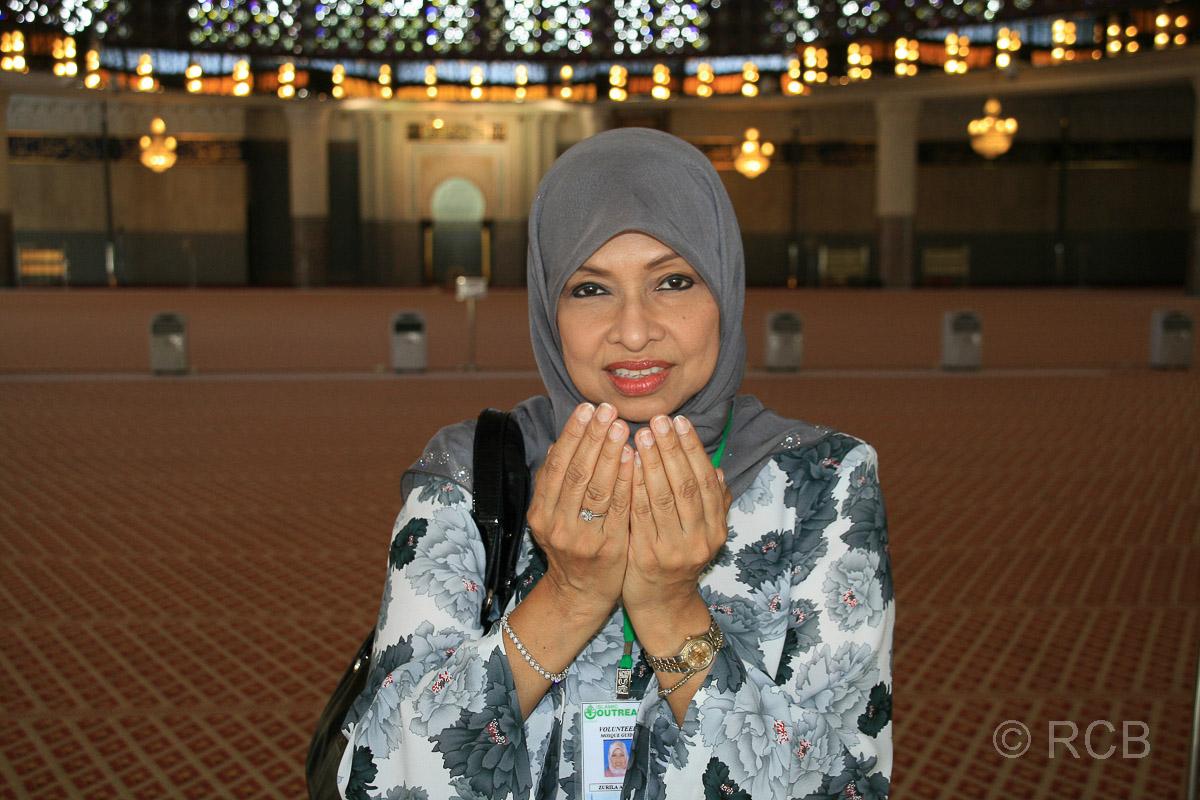 Frau formt die Hände wie beim Gebet im Gebetsraum der Nationalmoschee